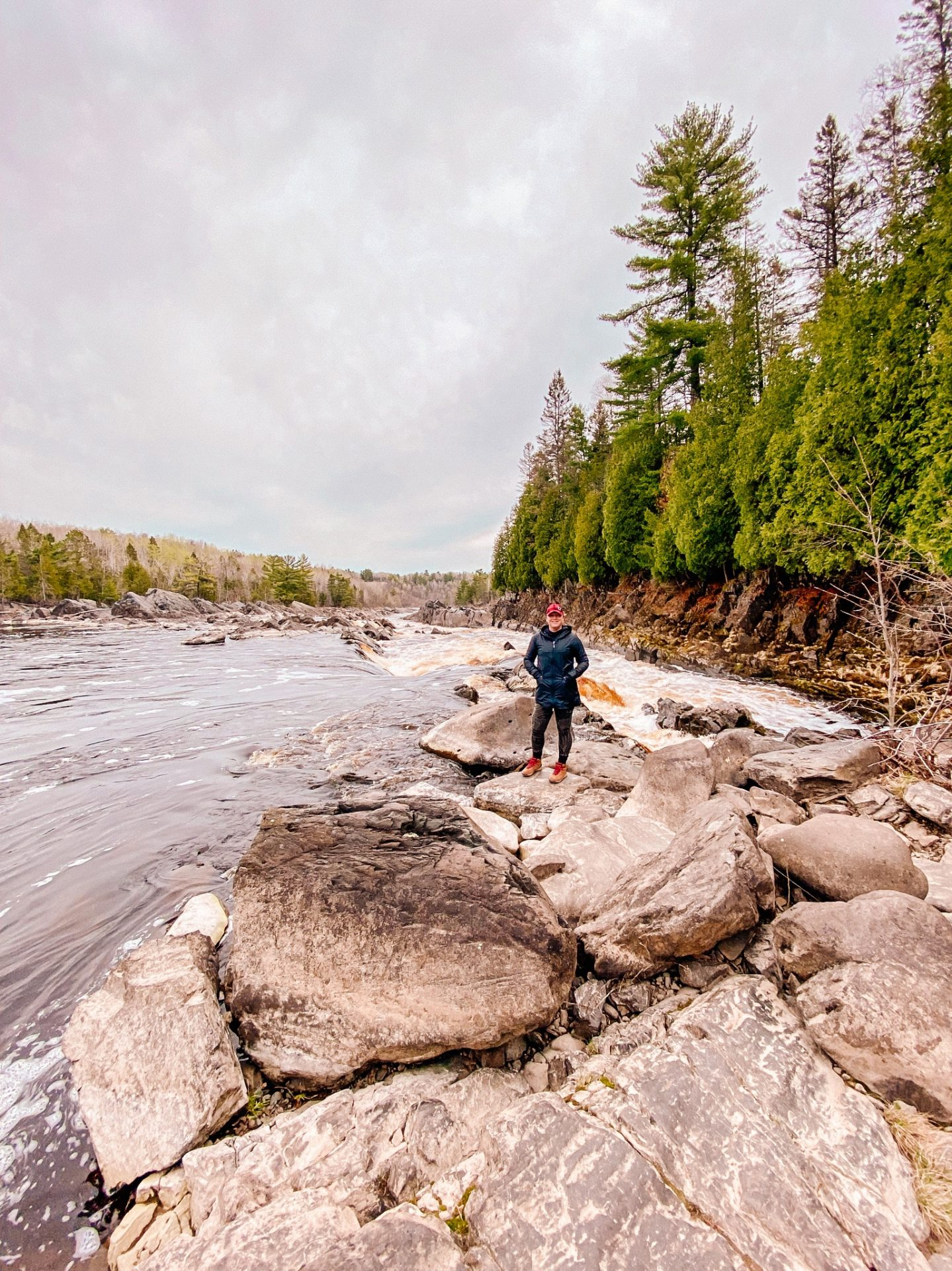 Woman standing on rocks near the St. Louis River at Jay Cooke State Park in Minnesota near Duluth while hiking. rugged river edge and green evergreen trees tower behind her.
