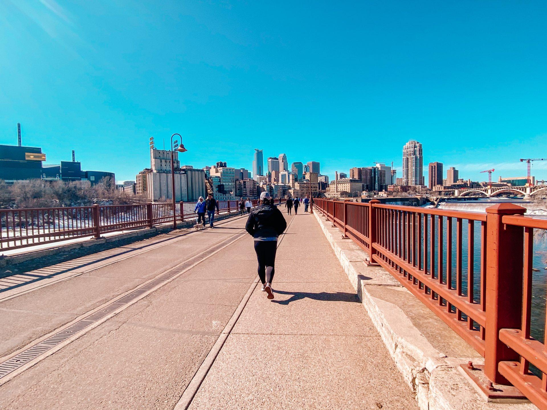 Woman walking toward Minneapolis on StoneArch pedestrian bridge