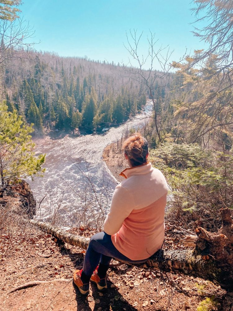 Woman staring out onto the falls and river at Tettegouche state park in Minnesota in the spring