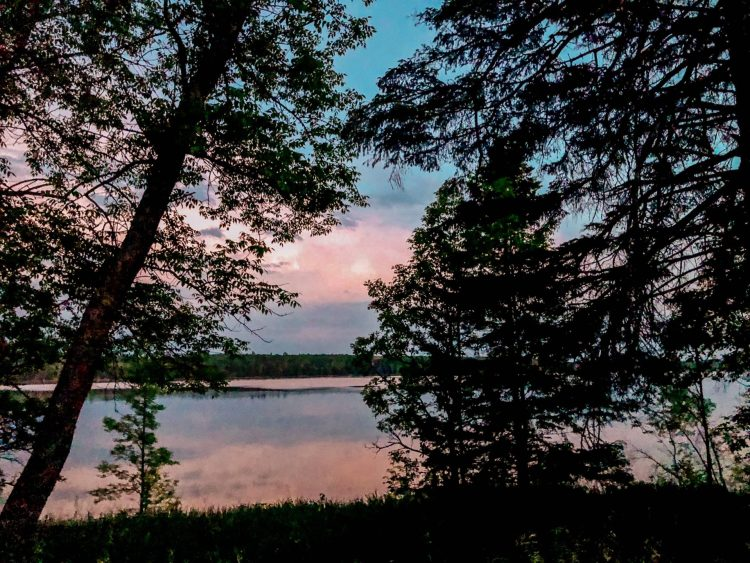 beautiful pink and colorful light blue sunset over a glass calm lake and trees towering in Northern Minesota in the summer