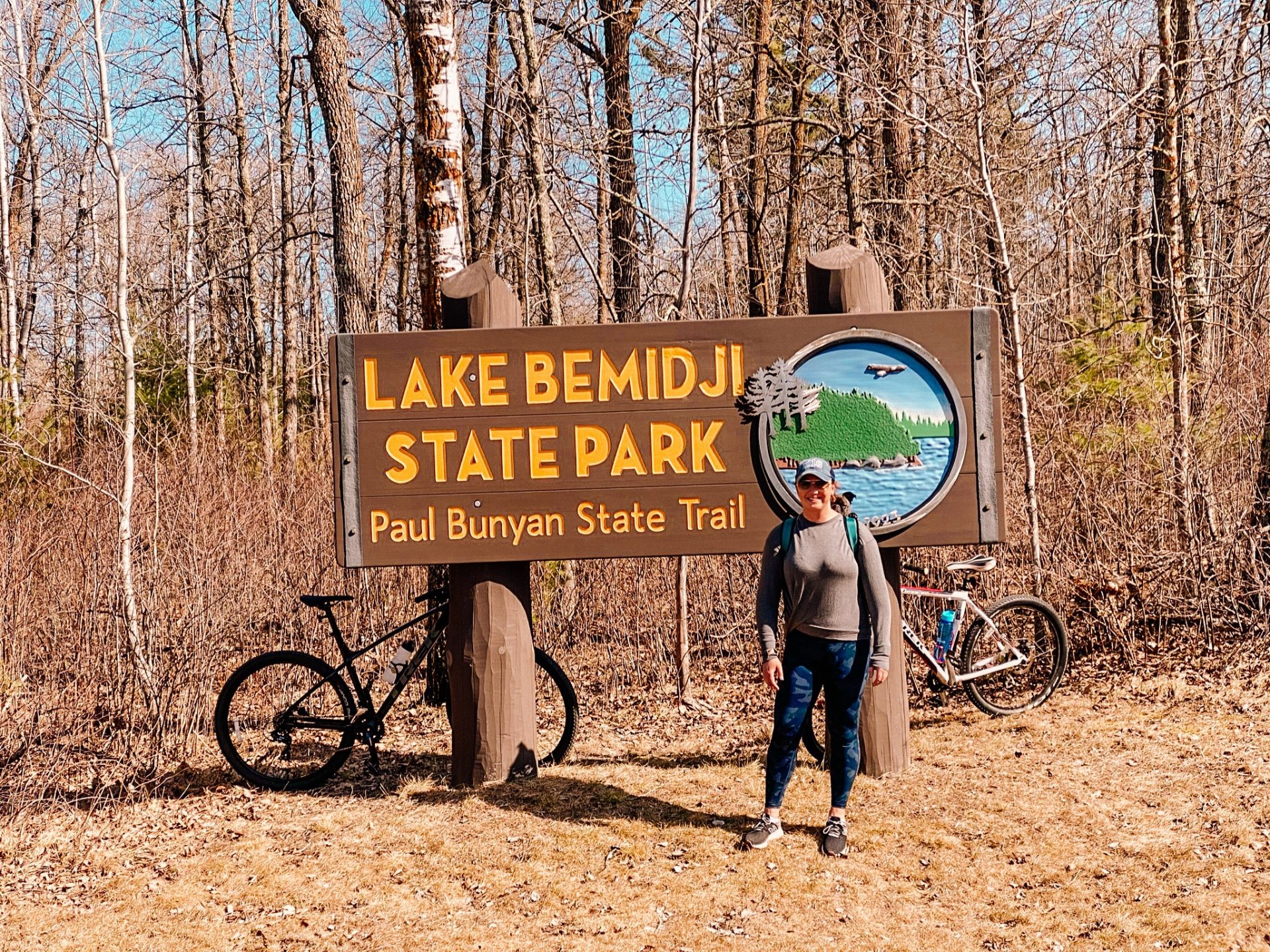 Woman standing in front of the Lake Bemidji State Park Paul Bunyan State Trail sign with a dog in a backpack carrier and two bikes propped up behind the sign.