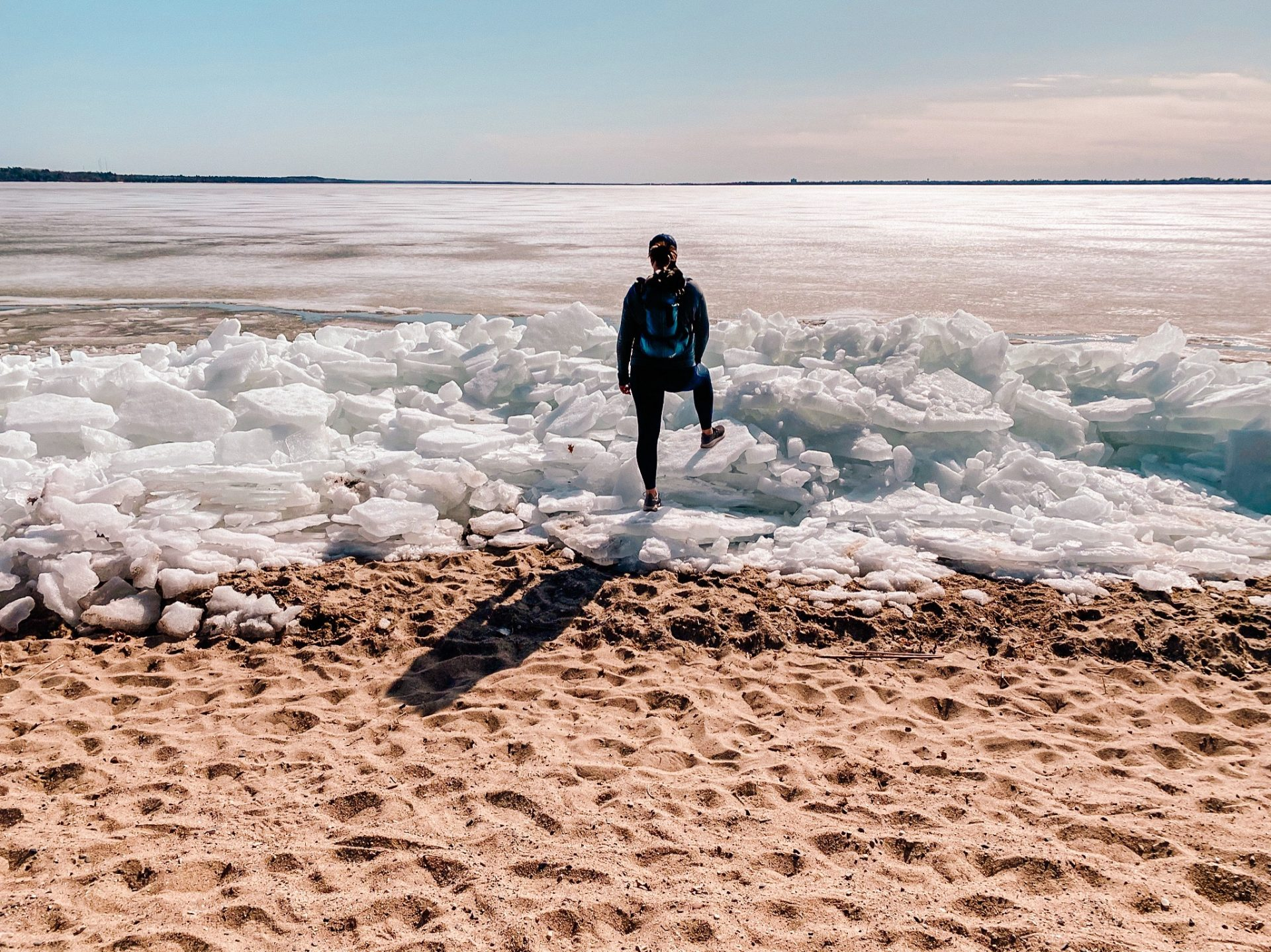 Ice coming off of Lake Bemidji in Minnesota at Lake Bemidji State Park. Woman standing on the ice shards along the lake shore sand.
