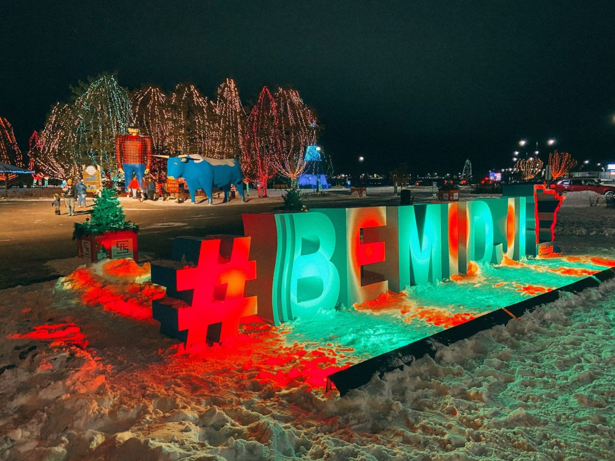 Bemidji, MN lake front during the holiday season. Trees with Christmas lights on them behind the Paul and Babe statues and lighted with green and red a #Bemidji with a Minnesota outline in front