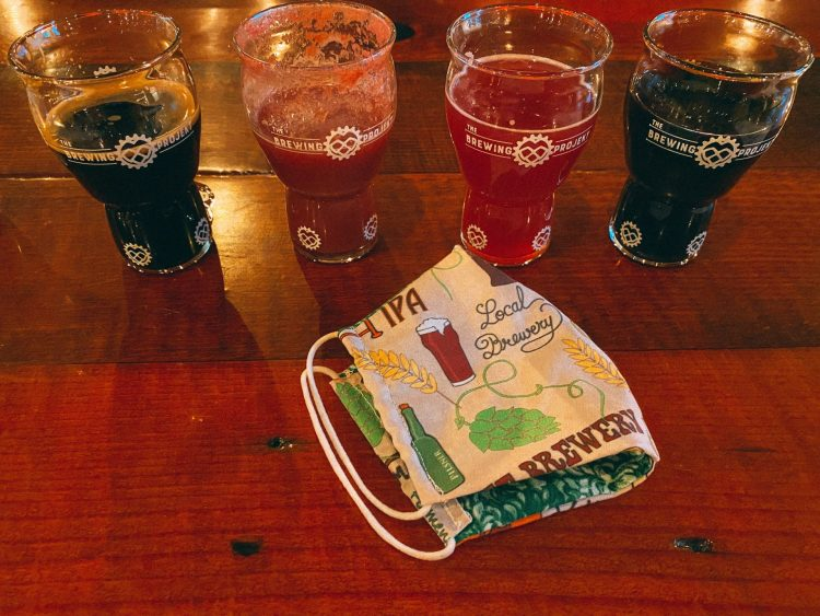 4 small beer taster glasses full of colorful pink and dark beers sitting on a wooden table with a beer fabric mask sitting by it