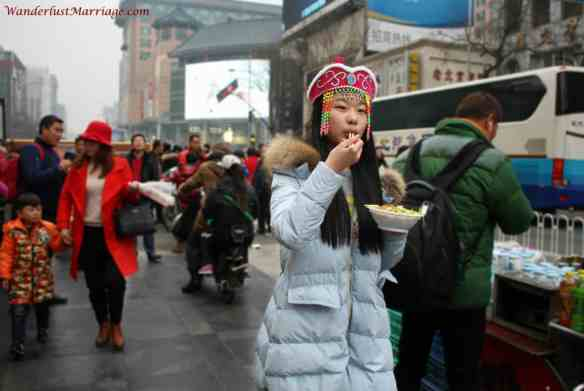 Chinese girl eating noodles, Beijing, China