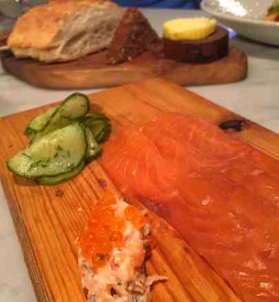 Board with smoked salmon and bread in background