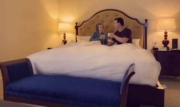 Alex & Bell in the hotel bed drinking their morning coffee