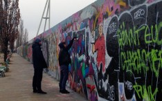 Graffiti artists spray painting a piece of the Berlin wall, which is actually legal now.