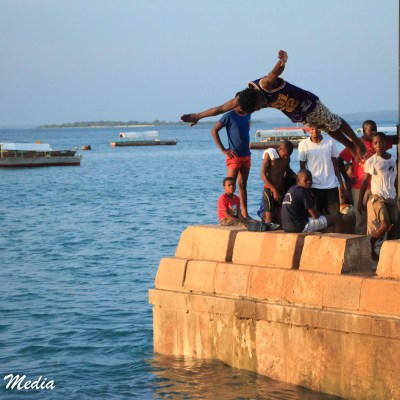 Kids escape the heat by jumping into the ocean near Stone Town