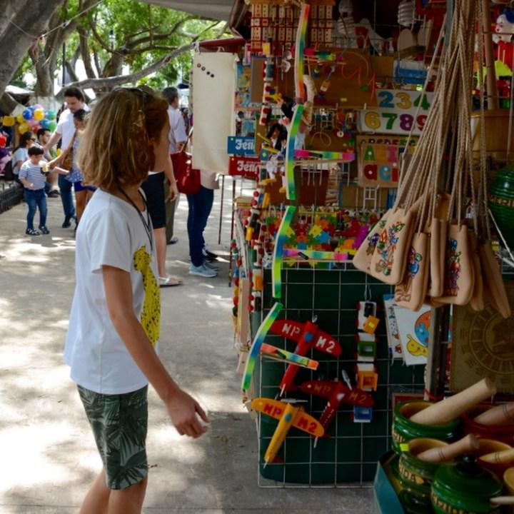 Travel with children kids mexico merida sunday market plaza grande toys