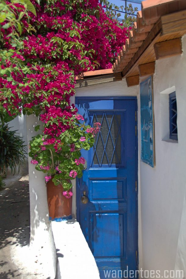 Blue door with cascade of pink flowers in Anafiotika, Plaka, Athens, Greece. Travel Photography