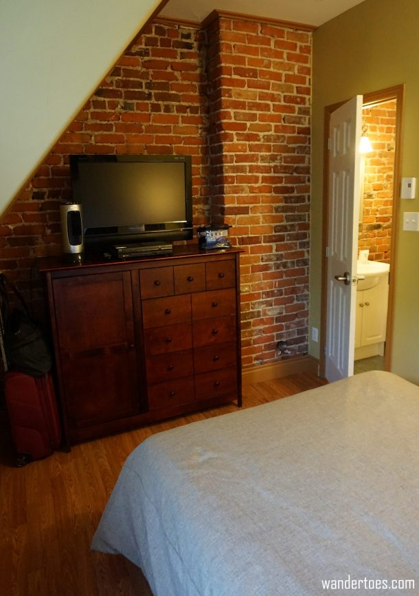 Hotel room with exposed brick wall and bathroom beyond.  Manoir de la Terrasse Quebec City Canada Review
