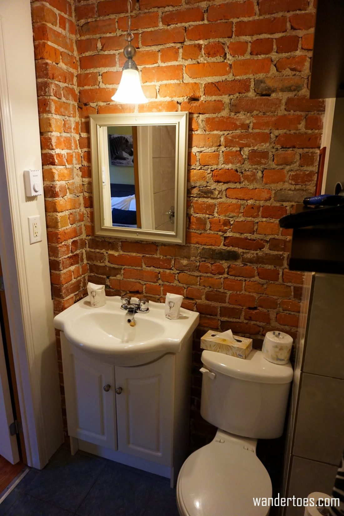 Updated bathroom with exposed brick wall.  Manoir de la Terrasse Quebec City Canada Review