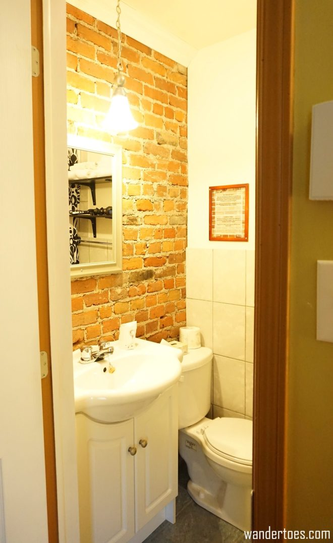 Updated bathroom with exposed brick wall.  Manoir de la Terrasse Quebec City Canada Review
