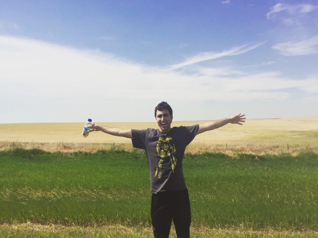 A travel friend spreading his arms wide out in the rolling fields of the country.