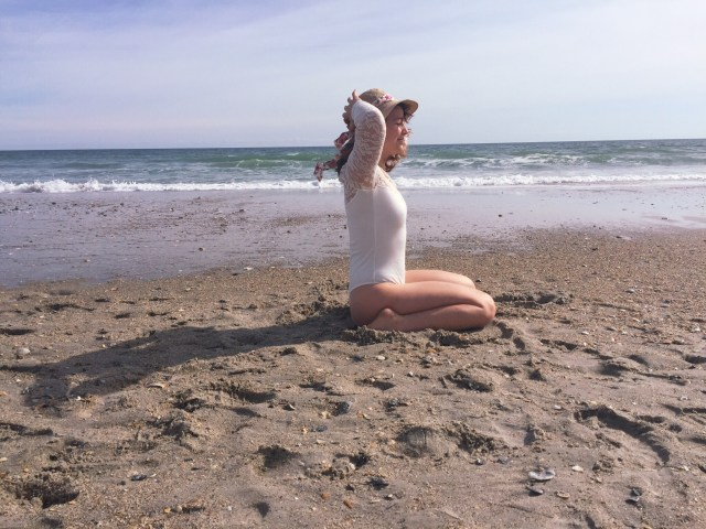 Woman meditating on the beach in Wilmington, North Carolina
