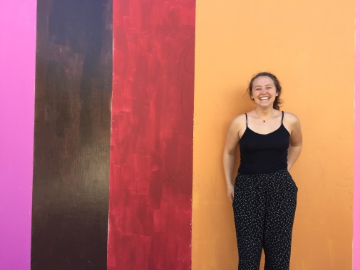 Girl laughing in front of a striped pink, brown, red and yellow wall.