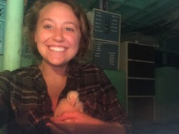 A woman holding a baby chick.