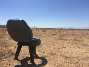 a toilet, plastic with no bottom, sitting in a desert field.