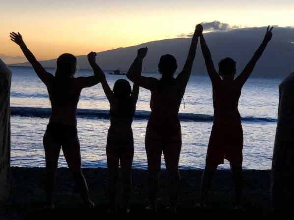 four people standing in front of a maui sunset