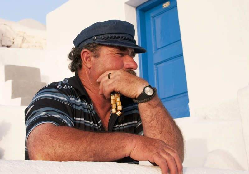 Greek man with prayer beads looking out to Aegean Sea, Oia, Santorini