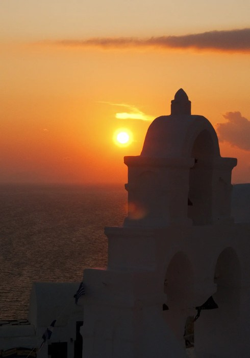 Sunset over Aegean Sea with chuch in foreground, Oia, Santorini, Greece
