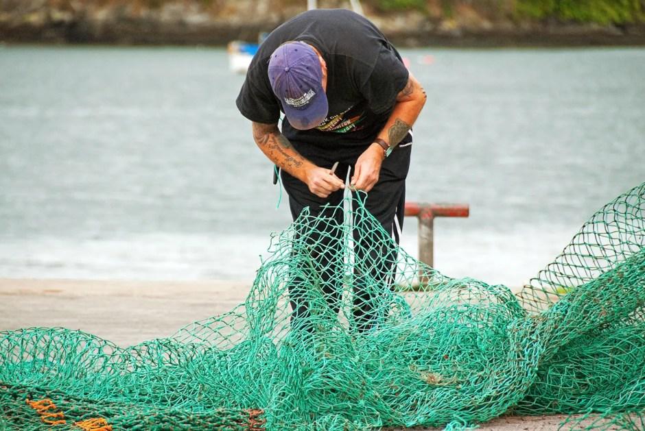 Man working on fishing net, Kinsale, County Cork, Ireland