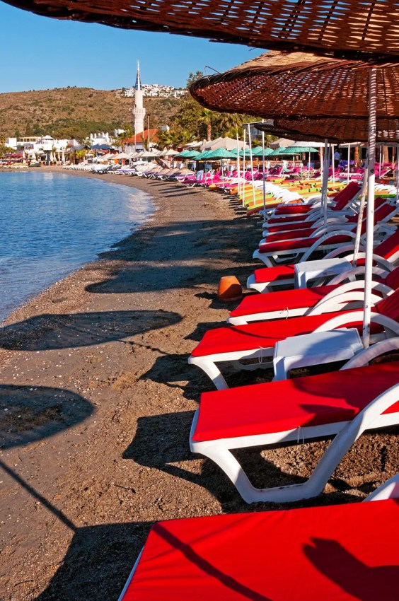 Colorful sun loungers on beach at Bitez, Bodrum Peninsula. Turkey