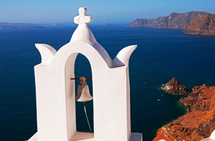 Church bell tower with Aegean Sea in background, Oia, Santorini, Greece
