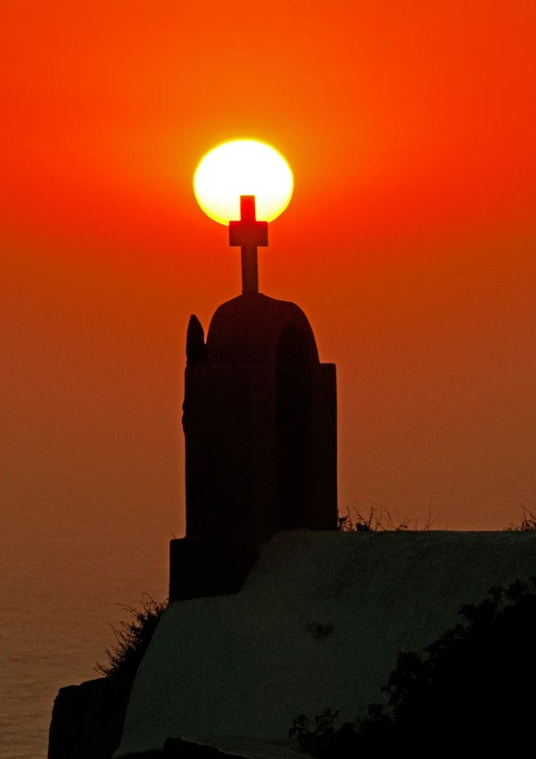 Sunset with silhouette of church cross in foreground, Oia, Santorini, Greece
