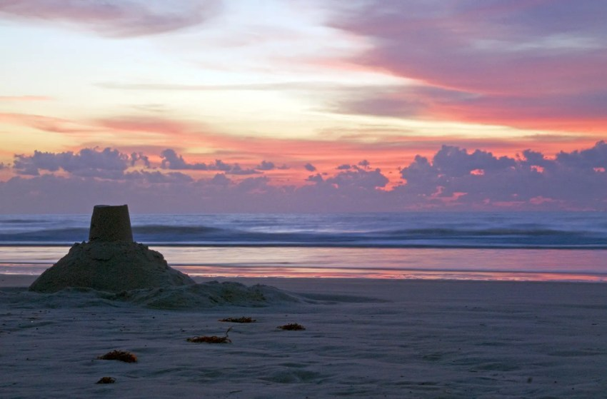 Sunrise at Cocoa Beach, Florida, with a sandcastle in the foreground and a dramatic sky