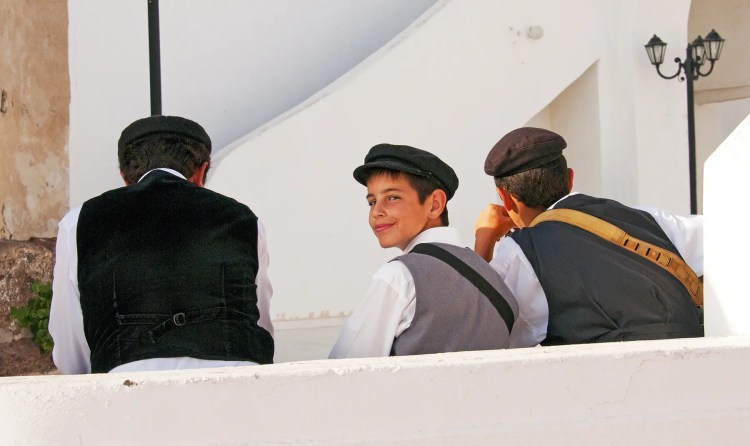 Young boy, part of a trio of musicians, at a wedding, Imerovigli, Santorini, Greece
