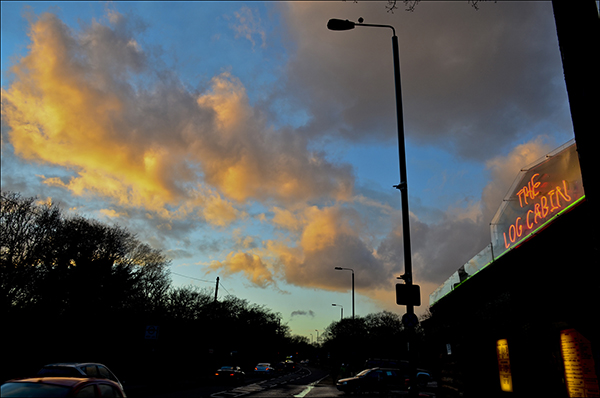 """© Geoff Wilkinson, who writes on his Wanstead Daily Photo blog: """"I was near Hollow Pond, Whipps Cross Road when the setting sun briefly lit up the clouds overhead . The Log Cabin cafe was close by and I spotted that the neon sign on the cafe was roughly the same colour as the illuminated part of the clouds. This for me made the picture."""""""