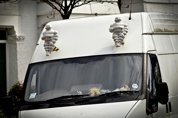 """© Geoff Wilkinson, who writes on Wanstead Daily Photo: """"Driving along Addison Road the other day I did a double take when I saw this white van. There sitting affixed to the front of the van were this pair of Michelin men, I haven't seen these for years, where have they been hiding? Michelin man is the symbol of the Michelin tyre company and was introduced at the Lyon Exhibition in 1894. It is one of the worlds oldest trademarks and always smiling."""""""