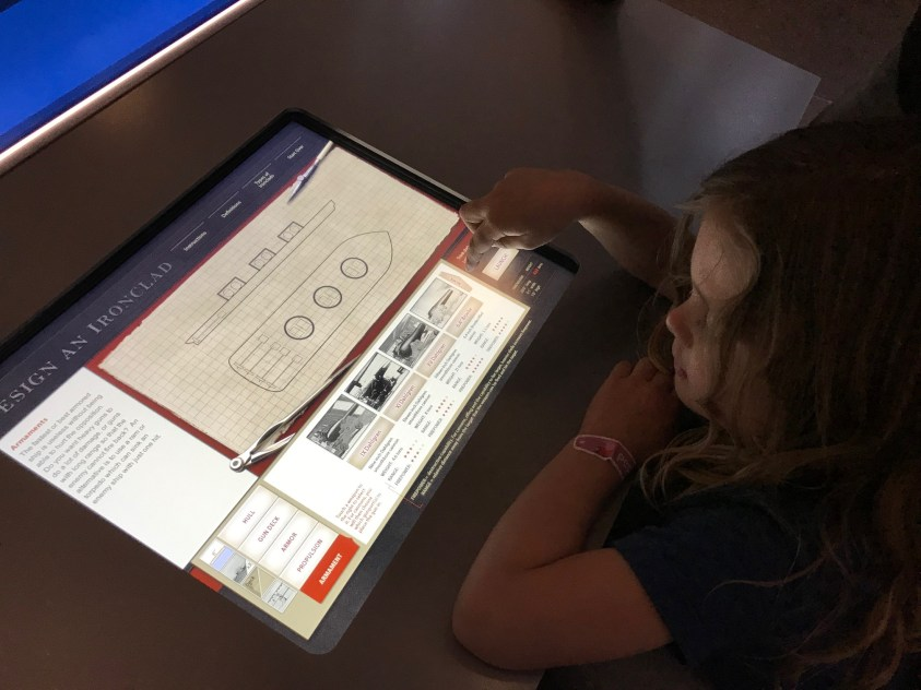 Granddaughter Jane Peterson designing a Civil War ironclad on an interactive display in the war museum.