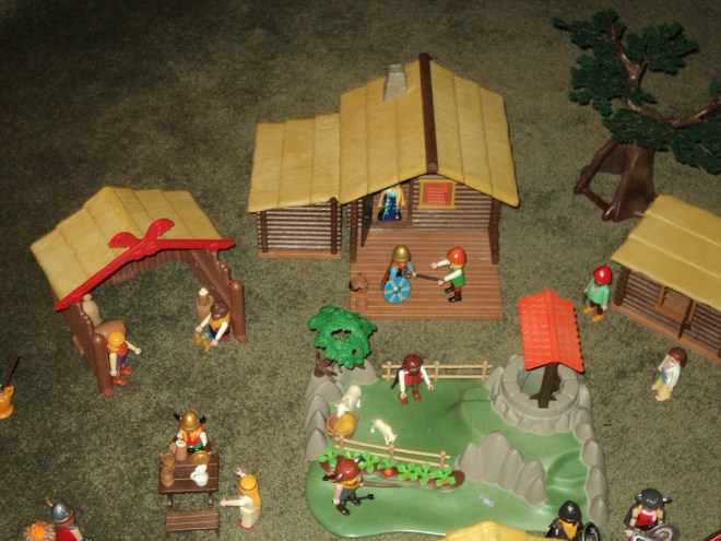 In the rear center of the Village is large Timber house, a small Timber house, and a small farm with a well.