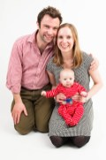 Studio photograph of young baby boy in bright clothes with his parents. Photographed by Anna Hindocha/Warm Glow Photo