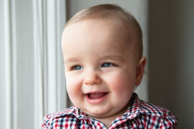 One year old boy smiling at window in his living room. Photographed by Anna Hindocha/Warm Glow Photo