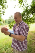 Father holding newborn baby in Belair Park, Dulwich. Photographed by Anna Hindocha/Warm Glow Photo