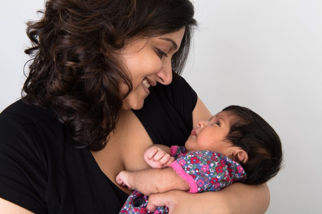 Studio photo of a newborn baby girl and her mother. Photographed by Anna Hindocha/Warm Glow Photo