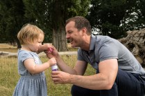 Toddler girl blowing bubbles with her father in Bushy Park, Teddington in autumn photographed by Anna Hindocha/Warm Glow Photo