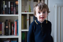 Young boy standing in front of bookcase on location family lifestyle shoot. Photographed by Anna Hindocha/Warm Glow Photo