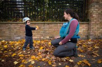 Young boy playing in autumn leaves with mother on location family lifestyle shoot. Photographed by Anna Hindocha/Warm Glow Photo