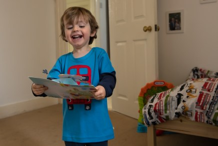 Young boy opening a birthday card on location family lifestyle shoot. Photographed by Anna Hindocha/Warm Glow Photo