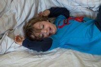 Young boy playing on his parents bed on location family lifestyle shoot. Photographed by Anna Hindocha/Warm Glow Photo