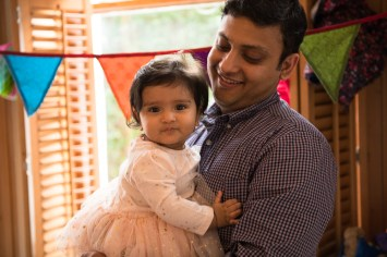 7 month old baby girl with her father in front of window.