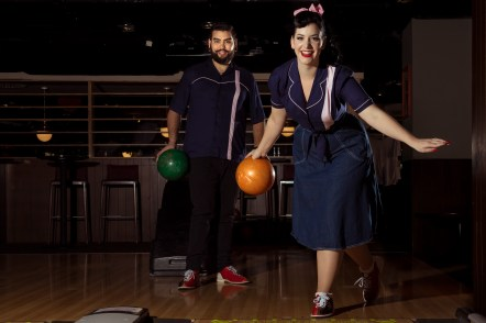 Couple in vintage style bowling shirts, bowling.