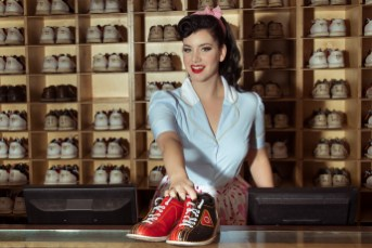 Woman in vintage style top handing out the shoes in a bowling alley.