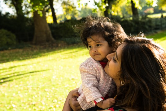 Young girl being held by mother in Battersea Park.