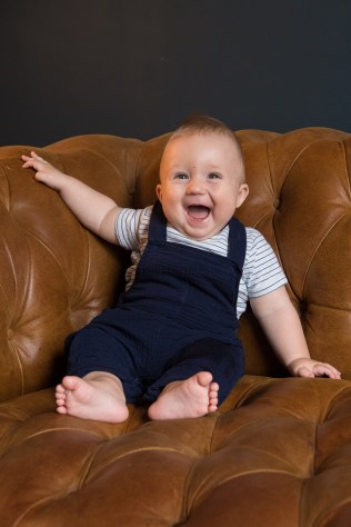 Baby sitting on sofa. Photographed by Anna Hindocha/Warm Glow Photo